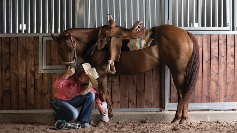 A girl in a pink shirt and cowboy hat is kneeling down looking up at a sorrel horse. (Credit: AQHA)