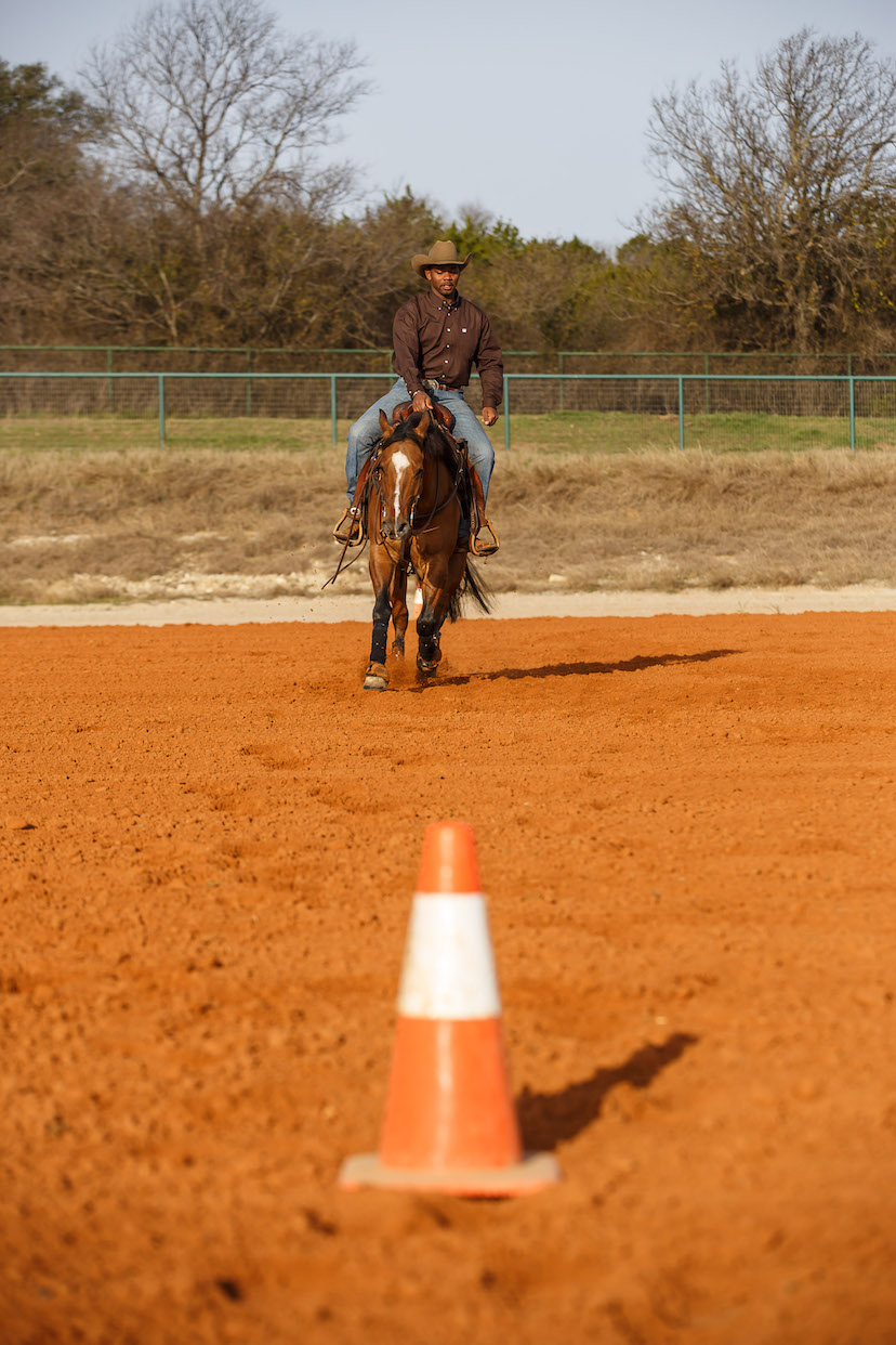 Ed Harrison and bay reining horse lope toward center marker