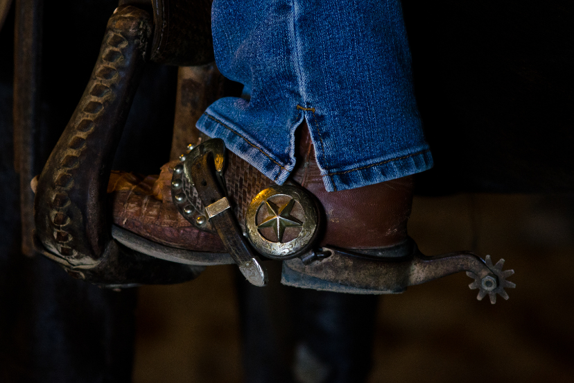 western spurs on boot in stirrup (Credit: Canva)