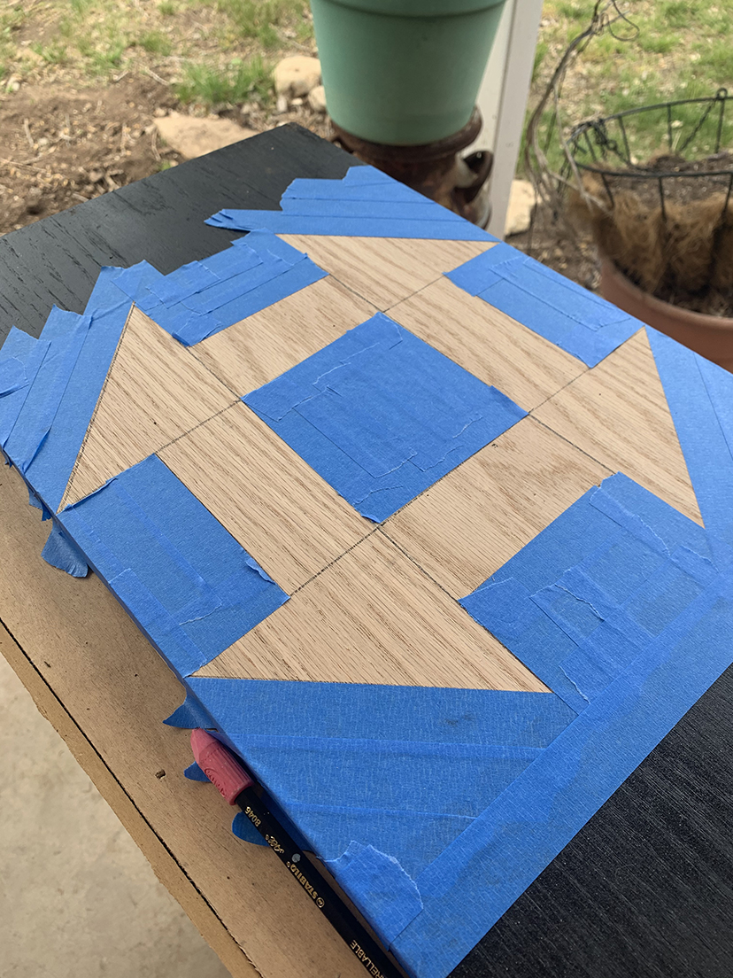 Board with blue masking tape outlining a churn-dash pattern.